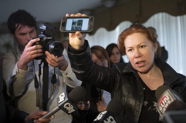 Maret Tsarnaeva, uma tia dos suspeitos,,segura um celular, que exibe uma foto do local da explosão, enquanto fala com jornalistas  (Foto: The Canadian Press, Chris Young/AP)