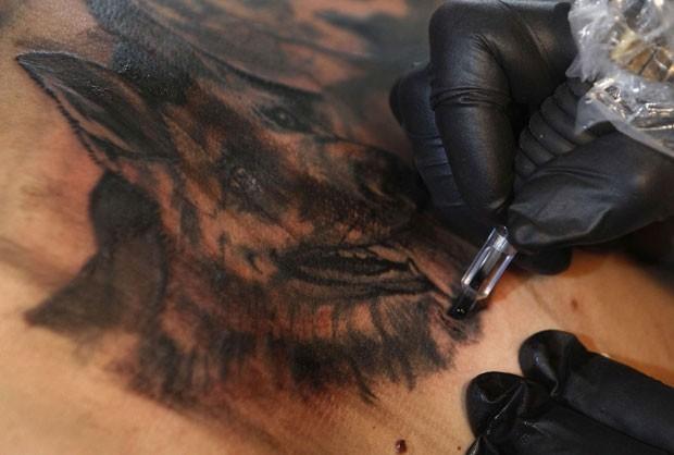 Em maio deste ano, um visitante tatuou nas costas a imagem de seu cão de estimação durante um evento de tatuagem em Atenas, na Grécia (Foto: John Kolesidis/Reuters)