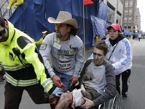 Jeff Bauman é resgatado por voluntários e membros das equipes de resgate após perder parte das duas pernas nas explosões em Boston (Foto: Charles Krupa/AP)