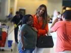 De terninho decotado, Nicole Bahls posa com fã em aeroporto
