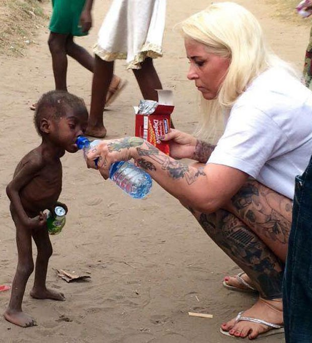 Anja Ringgren Lovén oferece água e biscoitos a Hope ao resgatar o menino das ruas, na Nigéria (Foto: Reprodução/Facebook/Anja Ringgren Lovén )