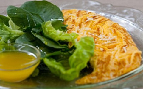 Omelete clássica com queijo servida com salada verde
