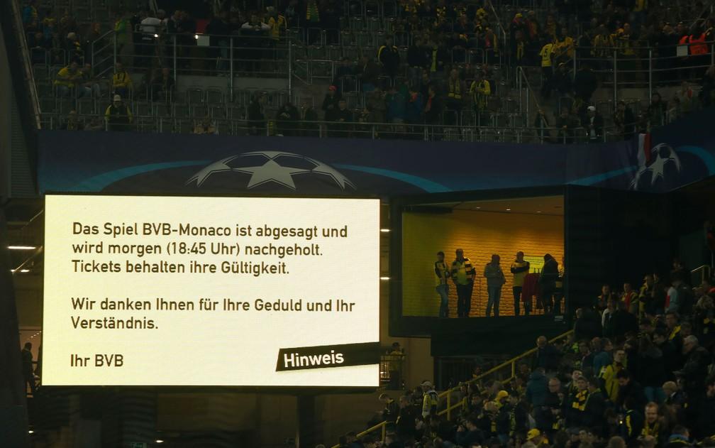 Telão dentro do estádio do Borussia Dortmund anuncia o adiamento da partida contra o Monaco, após explosão atingir o ônibus que transportava o time nesta terça (11) (Foto: Odd Andersen/AFP)