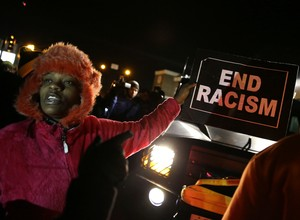 Manifestante pede o fim do racismo durante protestos contra a morte do jovem negro Michael Brown, em abordagem policial na cidade de Ferguson, Missouri (Foto: David Goldman/AP)
