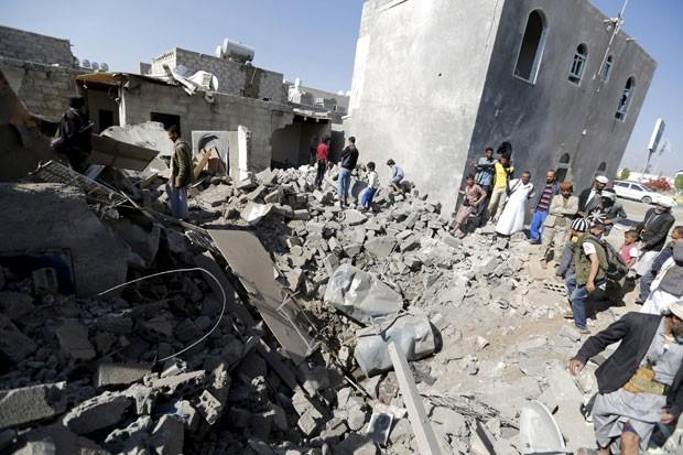 Pessoas são vistas nos destroços de casas que foram atingidas por um bombardeio perto do aeroporto de Sanaa nesta terça-feira (31) (Foto: Khaled Abdullah/Reuters)