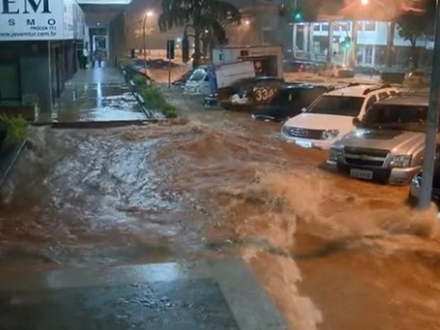Água quase ultrapassa altura de carros estacionados em quadra comercial da Asa Norte, em Brasília, depois de temporal (Foto: TV Globo/Reprodução)