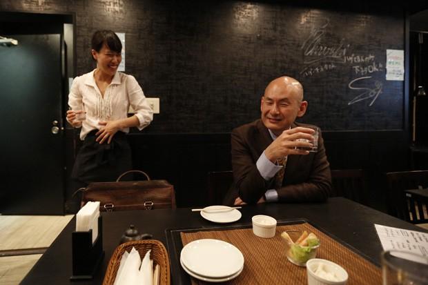Shiro Fukai, de 48 anos, bebe ao lado da gerente Yoshiko Toyoda no 'bar para carecas' em Tóquio, no Japão (Foto: Toru Hanai/Reuters)