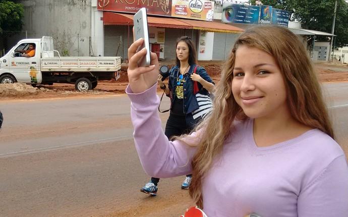 A estudante Eliandra Silva aguarda o ônibus quando foi surpreendida pela passagem do revezamento da chama olímpica (Foto: Fabiula Wurmeister)