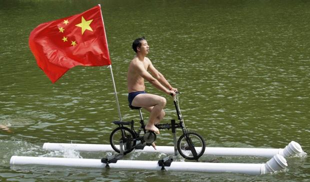 Liu Wanyong exibe sua bicicleta aquática em rio em Zhenning (Foto: Stringer/Reuters)