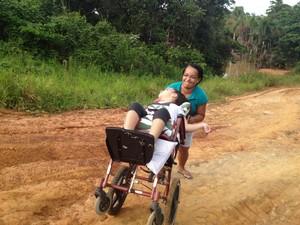 Maria do Socorro empurra cadeira de rodas da filha Vitória (Foto: Genival Moura/G1)