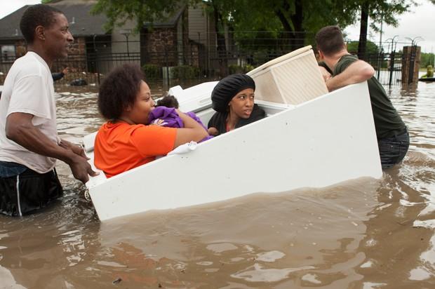 Voluntários usam freezer como barco para resgatar mulheres em Woodlands, perto de Houston, no Texas, (Foto: Brett Coomer/Houston Chronicle/AP)