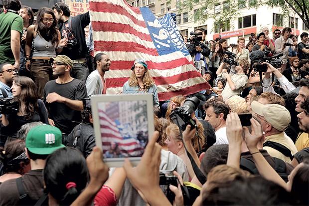 Ocupem Wall Street | 2011 O movimento popular contra a desigualdade nos Estados Unidos eclodiu em Nova York, em setembro de 2011. Seu nome permaneceu por dias entre os mais comentados no Twitter. A página dos manifestantes no Facebook chegou rapidamente a 500 mil fãs e diversas cidades no mundo tiveram suas versões do movimento.  (Foto: Stan Honda/AP)