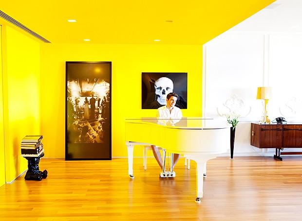 Um trecho do living foi inteiramente pintado de amarelo da Coral (ref. 37YY61/867), como uma caixa. Rosenbaum escolheu colocar o piano ali, deslocado da sala principal, para surpreender. Nas paredes, uma fotografia do casamento de Flávia e Otaviano e outra, de caveira, comprada na Micasa (Foto: The Selby)