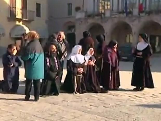 Padre e freiras rezam após serem retirados de igreja em Norcia, neste sábado (30), após tremor que atingiu região central da Itália (Foto: Sky Italia via AP)
