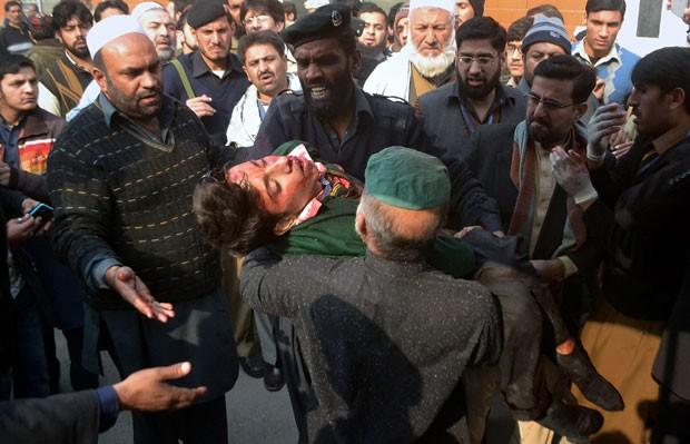 Feridos são retirados de escola que foi atacada pelo Talibã nesta terça-feira (16) no Paquistão (Foto: Mohammad Sajjad/AP)