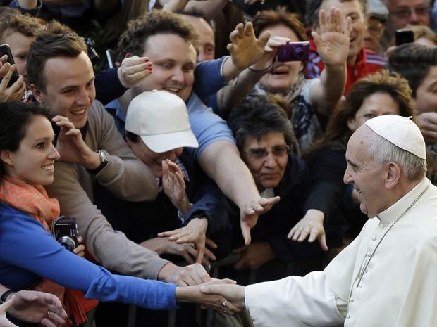 Papa cumprimenta uma das fiéis que o aguardavam do lado de fora da igreja (Foto: Gregorio Borgia/AP)