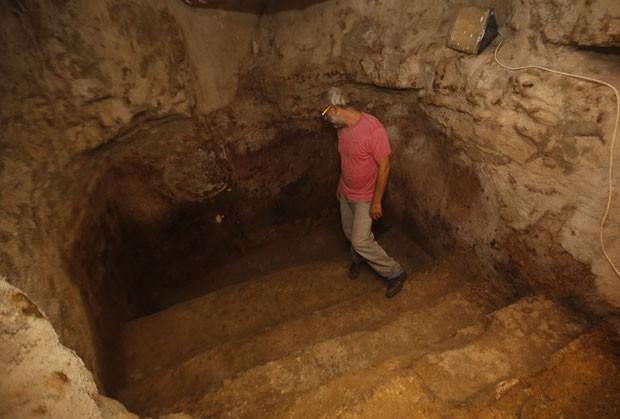 Homem mostra a piscina de imersão no banheiro milenar descoberto sob o piso de sua sala em Jerusalém (Foto: Gali Tibbon/AFP)