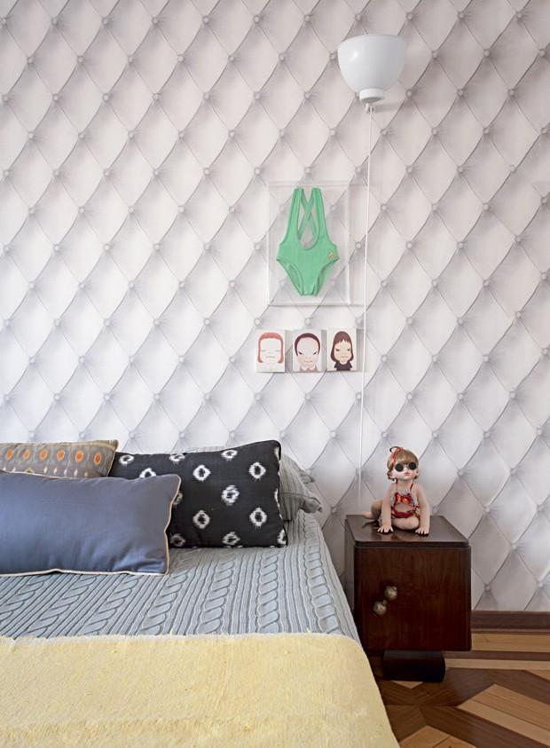 Quarto | O efeito capitonê do papel de parede dá sensação de conforto e dispensa cabeceira. No criado-mudo, boneca de porcelana numerada, e, acima dele, maiô da infância e quadrinhos de Yoshitomo Nara. Na cama, colcha de tricô da Mundo do Enxoval (Foto: Gui Morelli/Editora Globo)