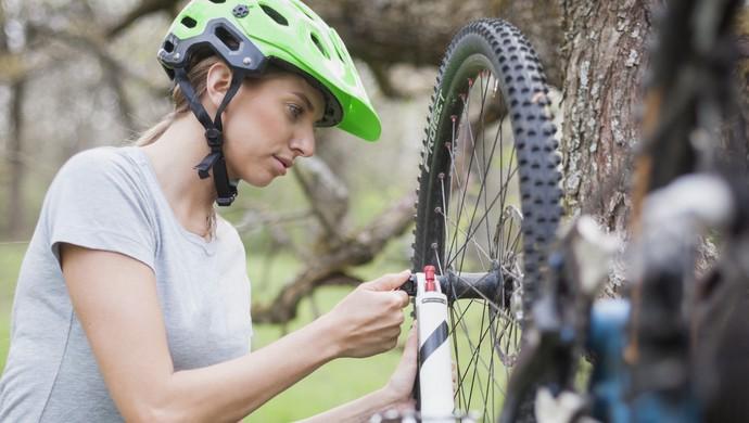 EuAtleta - mulher trocando pneu bicicleta (Foto: iStock Getty Images)
