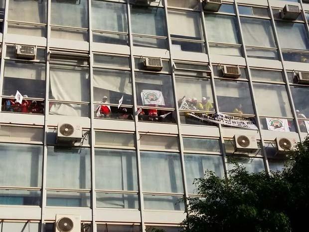 Manifestantes colocam faixas em janelas do Ministério da Fazenda durante protesto por melhorias no campo (Foto: Isabella Calzolari/G1)