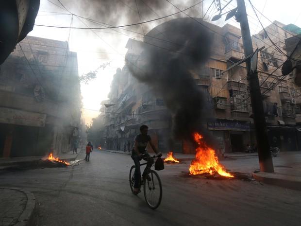 Homem anda de bicicleta em meio a barricadas em chamas em Aleppo, no norte da Síria, na segunda-feira (1º) (Foto: Abdalrhman Ismail/ Reuters)