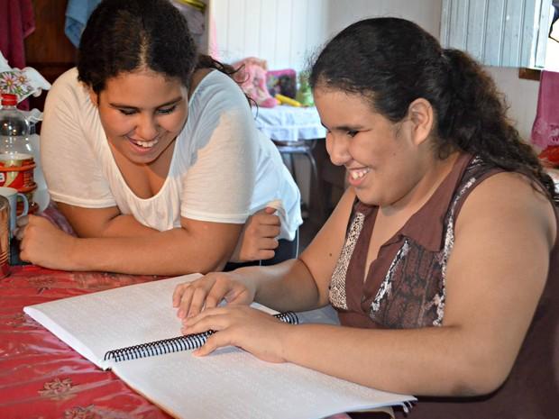 Katrinny é quem ajuda a irmã gêmea Kamilly na escola (Foto: Janine Brasil/G1)