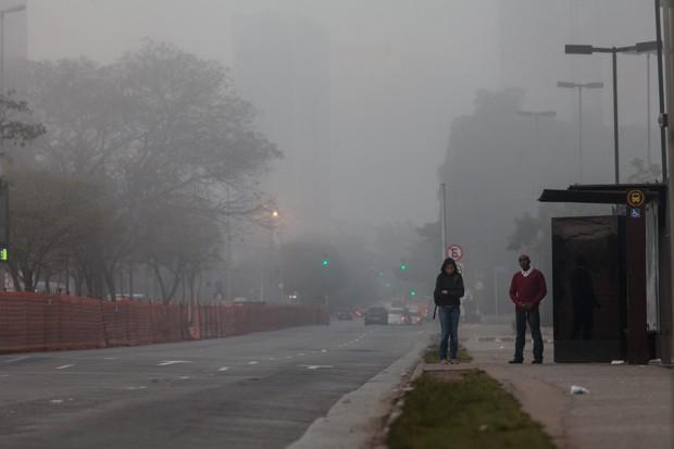 Pessoas aguardam no ponto de ônibus durante manhã fria e com névoa em São Paulo (Foto: Marcelo Brandt/G1)