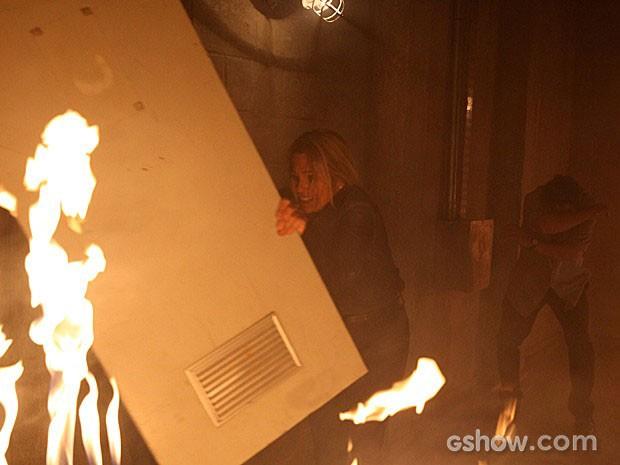 Thomaz usa uma porta para se defender do fogo (Foto: Além do Horizonte / TV Globo)