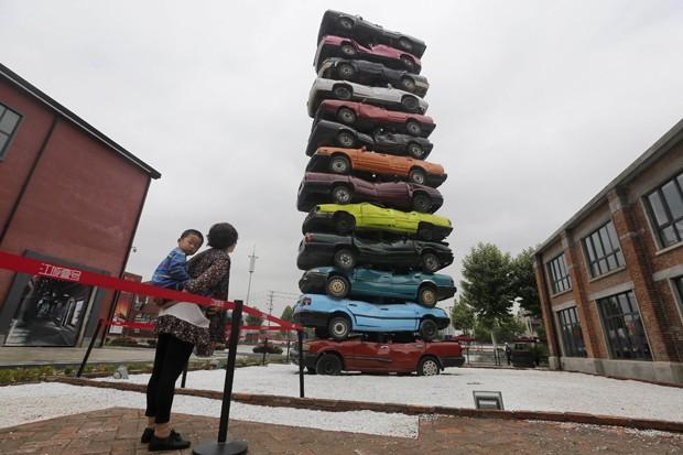 Artistas Sun Yeli e Gu Yuan utilizaram 13 carcaças de carros coloridos para montar escultura no parque industrial cultural em Wuhan, na província chinesa de Hubei (Foto: Stinger/Reuters)