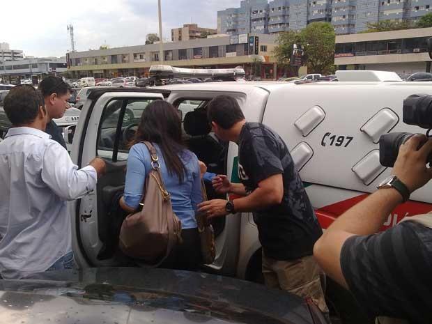 Funcionários da empresa que foram amarrados são levados pela polícia para serem ouvidos na delegacia (Foto: Felipe Néri / G1)