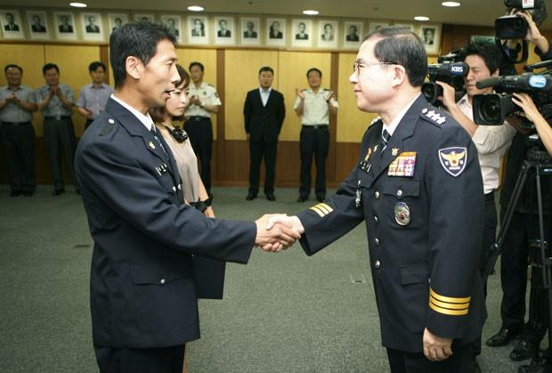 Kim Hyun-cheol (esq) recebeu promoção por sua atitude. (Foto: Busan Police Agency/AP)