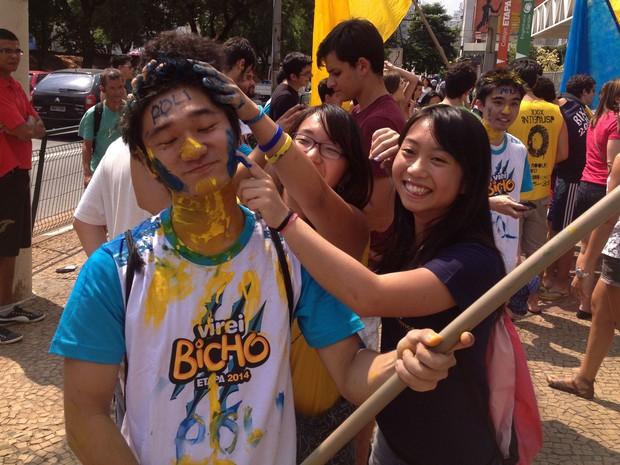 Vinicius Hideki Uehara é pintado pelas amigas após aprovação (Foto: Marina Franco/G1)
