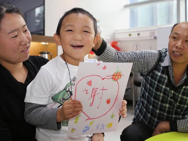 Guo Bin posa com os pais e um desenho do ideograma que representa a palavra 'obrigado' (Foto: C-Mer Dennis Lam Eye Hospital/AFP)