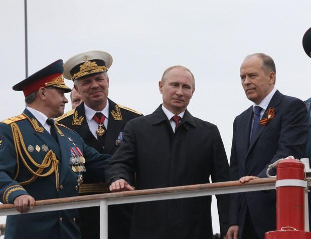 Putin e o ministro da Defesa russo, Sergei Shoigu, passam em revista navios da frota russa em Sebastopol durante visita à Crimeia nesta sexta-feira (9) (Foto: Maxim Shemetov/Reuters)
