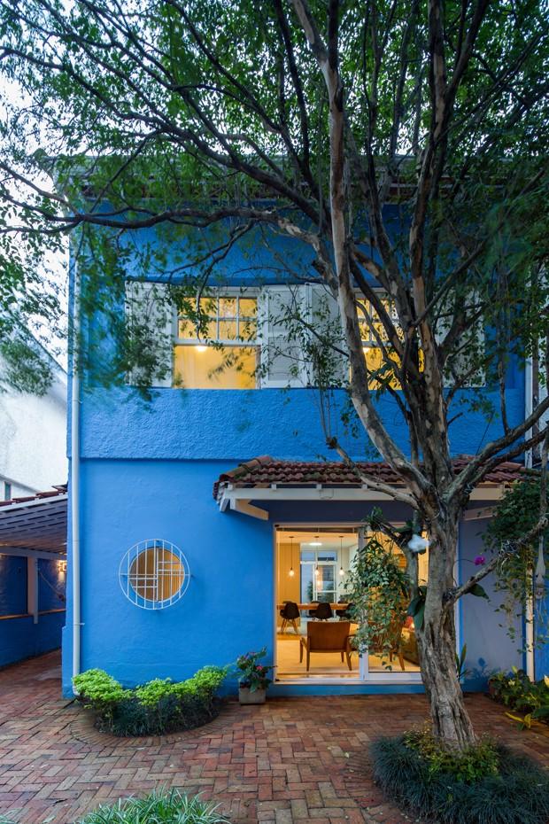 Fachada | Na entrada da casa é possível ver a porta de vidro instalada para priorizar a entrada de luz natural. A cor azul da fachada é da Suvinil (Foto: Pedro Napolitano Prata/Divulgação)