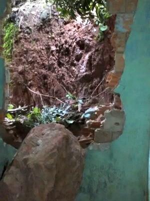 Pedra rolou pelo morro e invadiu casa após forte chuva (Foto: Major Raine Souza/Corpo de Bombeiros)