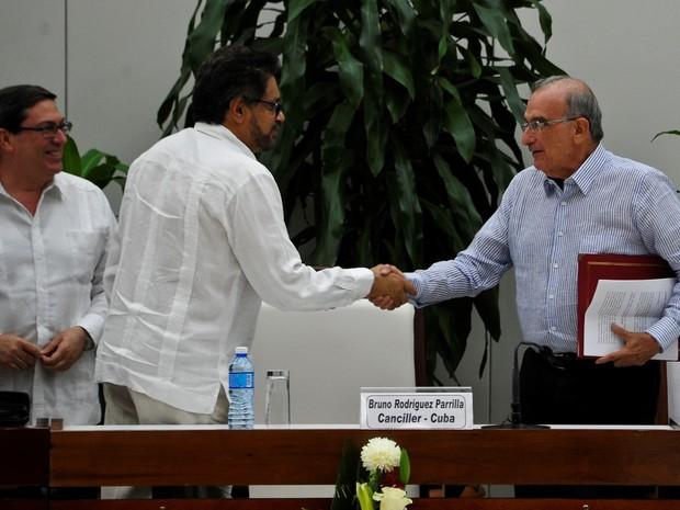 Chefe negociador das Farc, Iván Márquez, e Humberto de la Calle, chefe negociador da Colômbia, apertam as mãos em depois de assinar um novo acordo de paz entre a Colômbia e as Farc em Havana neste sábado (12) (Foto: Yamil Lage/AFP)