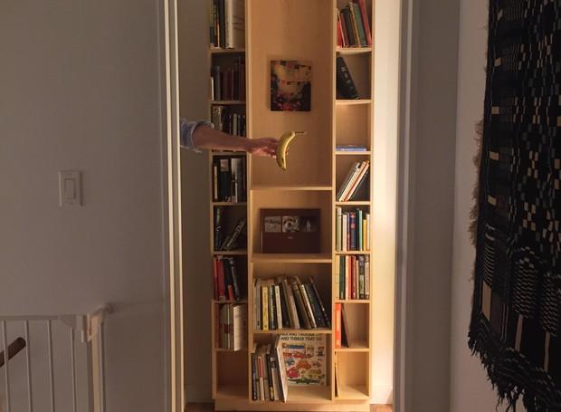 Quando aberta, a porta parece uma estante encostada na parede do corredor. O morador optou por decorar a estante com seus livros e quadros pessoais.   (Foto: Reprodução/ Imgur)