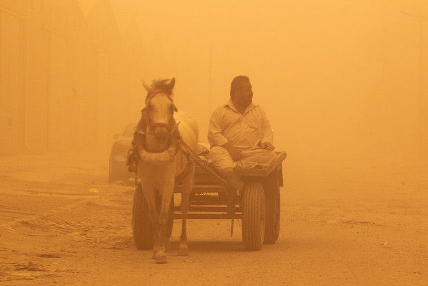 Homem conduz carroça em meio à tempestade de areia desta terça-feira (22) em Bagdá, capital do Iraque (Foto: Sabah Arar/AFP)
