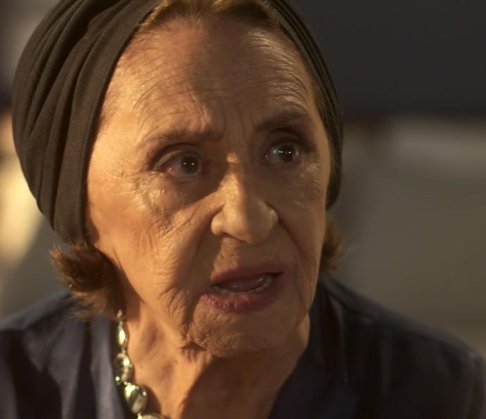 Dona Sinhá fica apavorada com a notícia que vê na TV (Foto: TV Globo)