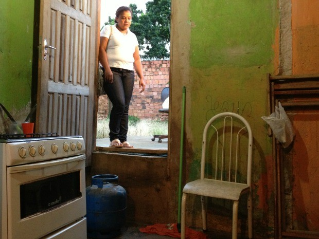 Cláudia Regina aterrou tantas vezes o seu quintal para tentar impedir a água de entrar, que o batente da porta está muito abaixo do terreno (Foto: Larissa Matarésio/G1)