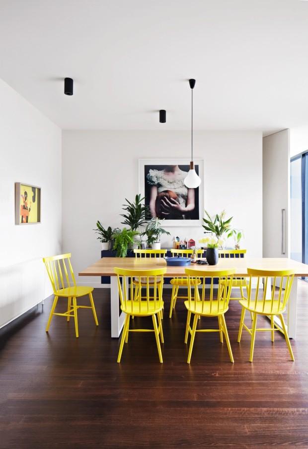 Jantar. As cadeiras amarelas em volta da mesa e as obras de arte na parede deram personalidade ao espaço (Foto: Armelle Habib / Living Inside)