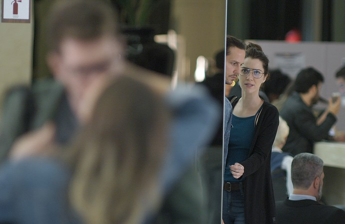 Júlia e Gui espiam Alex com sua vítima no aeroporto (Foto: TV Globo)