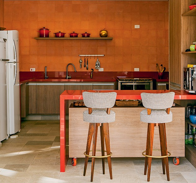 O laranja foi escolhido para esta cozinha, projeto do escritório Arkitito. Os ladrilhos da parede, as bancadas da pia e de apoio e até as panelas expostas exploram tons da cor