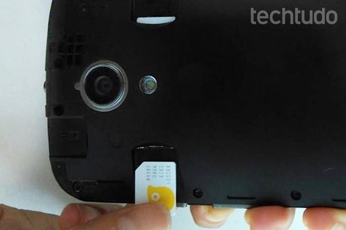 Chip transformado em micro SIM sendo inserido no celular  (Foto: Reprodução/Raquel Freire)