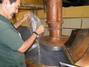 Láerico Shyia adiciona o lúpulo durante o processo de fabricação da cerveja (Foto: Taiga Cazarine/G1)