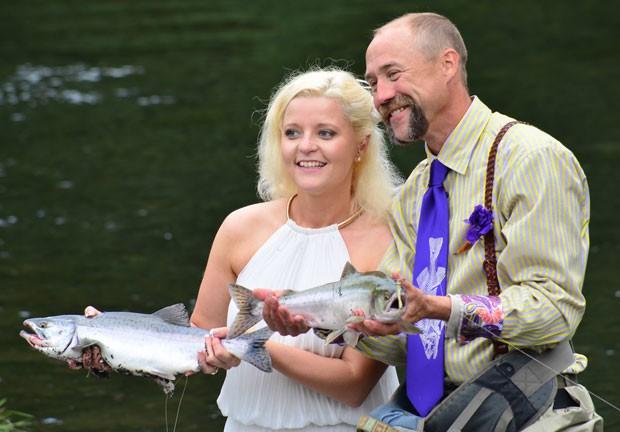 Kadie e Dake Schmidt  posam com dois salmões que eles fisgaram logo após a cerimônia (Foto: James Brooks/Kodiak Daily Mirror/AP)