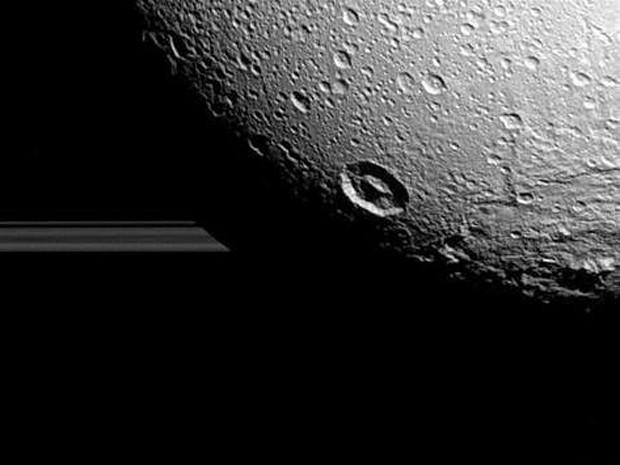 A lua Dione fotografada pela sonda Cassini com os anéis de Saturno ao fundo (Foto: Nasa)
