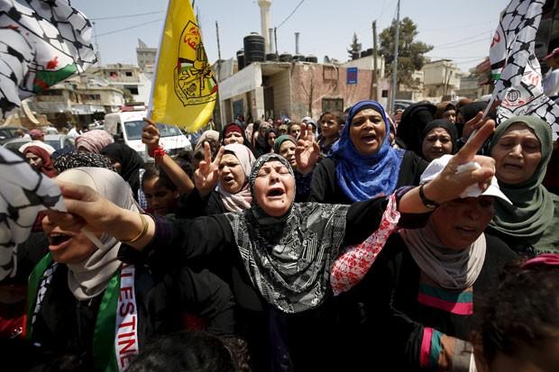 Mulheres palestinas gritam neste sábado (1º) durante protesto no funeral do bebê que morreu queimado em um incêndio em uma casa na Cisjordânia (Foto: Mohamad Torokman/Reuters)