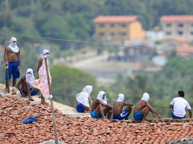 Presos são vistos no telhado da penitenciária de Alcaçuz, no Rio Grande do Norte, durante rebelião (Foto: Andressa Anholete/AFP)